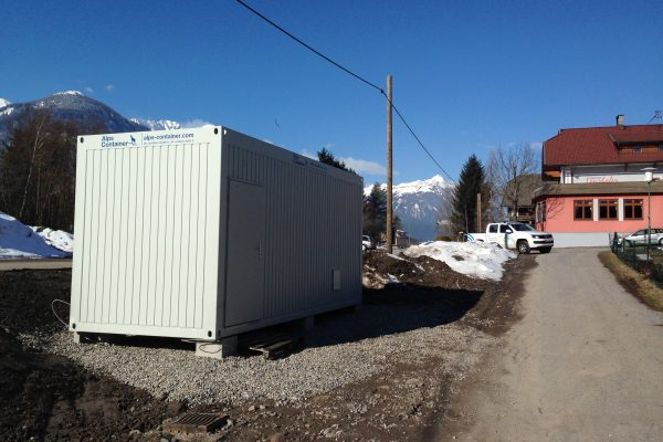 Baucontainer mit PickUp im Hintergrund